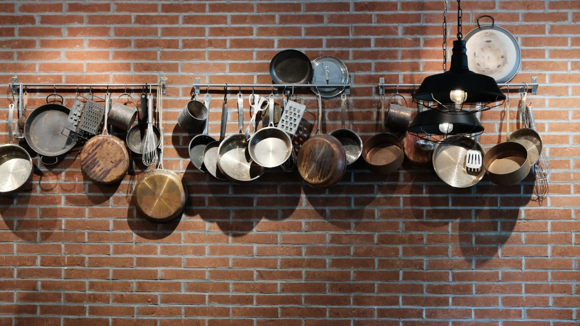 pots and pans hanging on a red brick wall